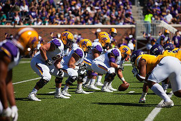 HSU football players setting up play at a game