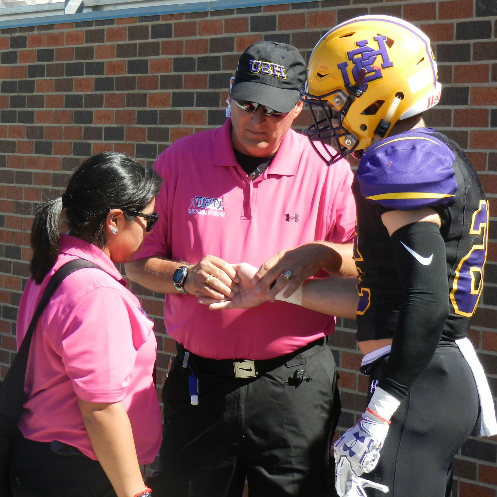 An athletic training professor wraps a football player's wrist as a student trainer observes.