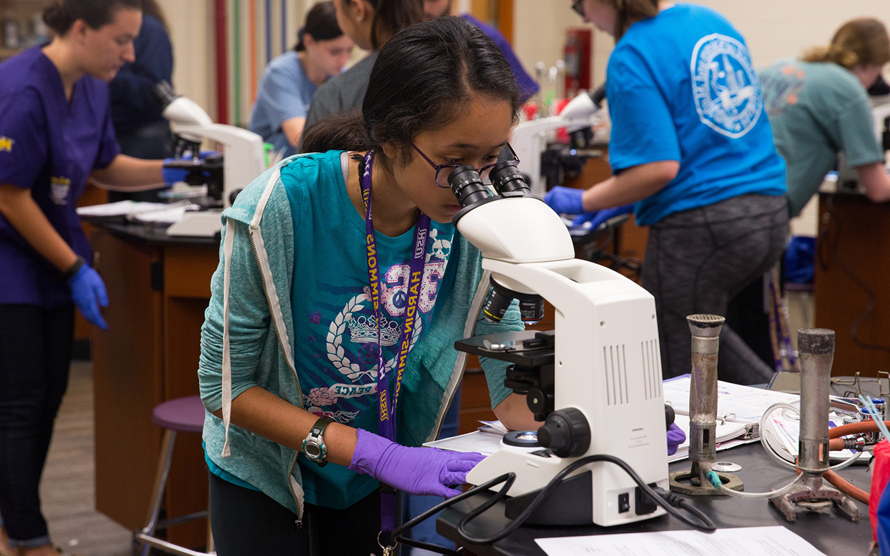 Photo of HSU student looking through microscope in laboratory.